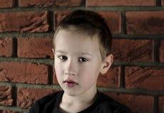 Jonge jongen die in zwarte t-shirt de camera bekijken Close-upportret op leuk boy'sgezicht die zich voor rode baksteenachtergro royalty-vrije stock fotografie