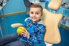 Jonge jongen in een tandchirurgie met aplle in zijn hand Royalty-vrije Stock Foto