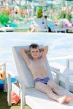 Jonge jongen in een zwempak op een plank door de pool royalty-vrije stock afbeelding