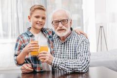 Jonge jongen en zijn grootvader het stellen met glazen jus d'orange en het kijken Stock Foto