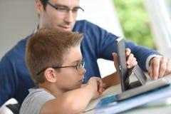 Jonge jongen en zijn vader die tablet gebruiken stock afbeelding
