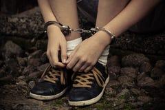 Jonge jongen in handcuffs en tennisschoenen Royalty-vrije Stock Afbeelding