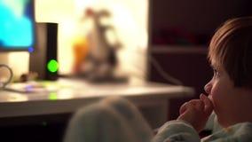 Jonge Jongen het Letten op Beeldverhalen in een Donkere Zaal op een Computer stock videobeelden