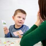 Jonge jongen in logopediebureau Kleuter die correcte uitspraak met toespraaktherapeut Child Occupational Therapy uitoefenen stock afbeelding