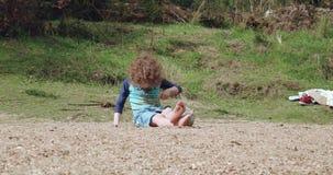 Jonge jongen met blond krullend haar die blauwe swimwear zitting op een rivierstrand dragen stock video