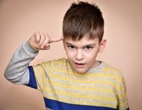 Jonge jongen met de wijsvinger op zijn hoofd royalty-vrije stock afbeeldingen