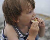 Jonge jongen met een plak van appel Stock Afbeelding