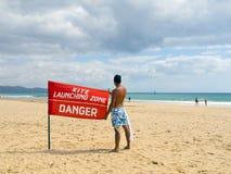 Jonge jongen met een rode vlag in het strand royalty-vrije stock foto