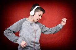 Jonge jongen met hoofdtelefoons die en van muziek genieten dansen Royalty-vrije Stock Foto's