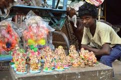 Jonge jongen met kleine Ganesha-Standbeelden Stock Foto's