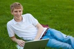 Jonge jongen met laptop computer buiten het zitten op gras Stock Afbeelding