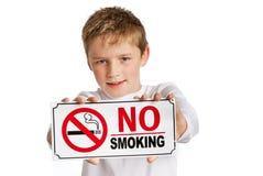Jonge jongen met no-smoking teken. stock foto
