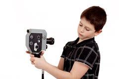 Jonge jongen met oude uitstekende analoge 8mm camera stock fotografie