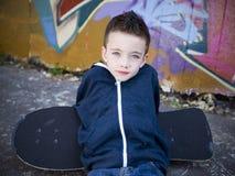 Jonge jongen met skateboard tegen een graffitimuur Stock Foto's