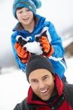 Jonge Jongen ongeveer om Sneeuwbal op het Hoofd van Vaders te laten vallen royalty-vrije stock afbeelding