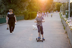 Jonge jongen op een autoped in het park Stock Fotografie