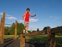 Jonge jongen op een evenwichtsbalk Stock Fotografie