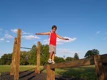 Jonge jongen op een evenwichtsbalk Stock Afbeeldingen