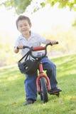 Jonge jongen op fiets die in openlucht glimlacht Stock Fotografie