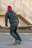 Jonge jongen op het skateboard in een stadsstraat stock fotografie