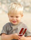 Jonge jongen op het strand met telefoon Stock Fotografie