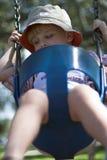 Jonge jongen op schommeling bij speelplaats Stock Foto's