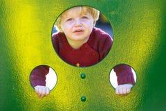 Jonge jongen of peuter die door gaten in een muur in een speelplaats kijken stock fotografie