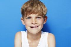Jonge jongen in studio, op blauwe achtergrond Royalty-vrije Stock Fotografie