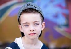 Jonge jongen tegen graffitimuur Stock Afbeeldingen
