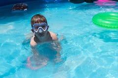 Jonge jongen in zwemmend masker in zwembad met groene vlotter stock foto's