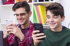 Jonge jongens die mobiele telefoons bekijken royalty-vrije stock fotografie