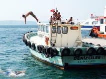 Jonge jongens die in water van een boot springen royalty-vrije stock afbeeldingen