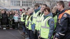 Jonge jongens en meisjes in emercomjasjes met rugzakken op straat teens publiek stock video