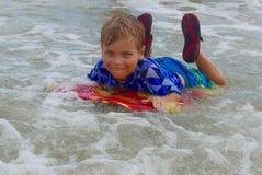 Jonge jongensbuik die op een boogieraad surfen in ondiep water royalty-vrije stock afbeeldingen