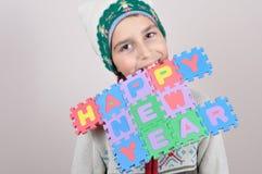 Jonge jongensholding in zijn tanden een Gelukkig Nieuwjaarteken Stock Afbeeldingen