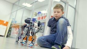 Jonge jongensingenieur die zelf-gemaakte robot testen bij technieklaboratorium stock video