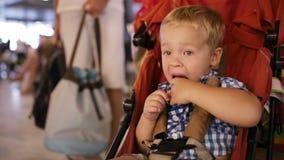 Jonge jongenszitting in een kindkarretje in een luchthaven stock video