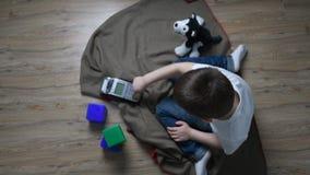 Jonge jongenszitting op de vloer die pos eindknopen drukken Moderne technologieën voor jonge geitjes Pos machinepraktijk Jonge ge stock video