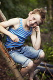 Jonge jongenszitting op houten laatstgenoemde, het glimlachen Stock Foto