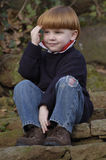 Jonge jongenszitting op treden Stock Foto
