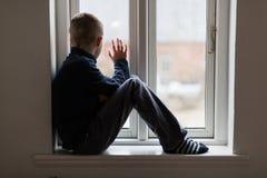Jonge jongenszitting op vensterbank het golven Royalty-vrije Stock Afbeeldingen