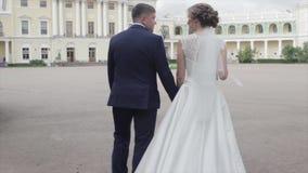 Jonge jonggehuwden die buiten lopen De bruid en de bruidegom lopen samen in het Park in de winter of de zomer en holdingshanden stock videobeelden