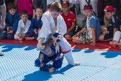 Jonge judoworstelaars 8-10 jaar op de demonstratieprestaties Stock Foto's