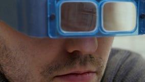 Jonge juweliermeester die de kwaliteit van gemmen controleren door glazen stock foto's