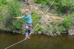 Jonge kabel-leurder die saldo proberen te houden terwijl het lopen op een kabel over Dnipro-rivier in centrum van dezelfde naamst royalty-vrije stock foto's