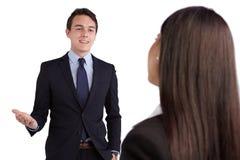 Jonge Kaukasische bedrijfsman die gelukkig aan een bedrijfsvrouw glimlachen Royalty-vrije Stock Afbeeldingen