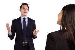 Jonge Kaukasische bedrijfsman die gelukkig aan een bedrijfsvrouw glimlachen Royalty-vrije Stock Fotografie