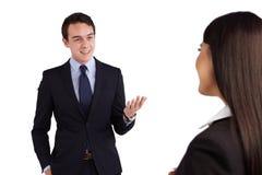 Jonge Kaukasische bedrijfsman die gelukkig aan een bedrijfsvrouw glimlachen Stock Afbeeldingen