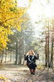 Jonge Kaukasische blondevrouw in bruine cardigan die een schommeling in gele de herfst bos Verticale richtlijn berijden royalty-vrije stock afbeeldingen