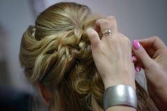 Jonge Kaukasische blondevrouw die haar die haar hebben voor het huwelijk of een formele gebeurtenis wordt gedaan stock foto
